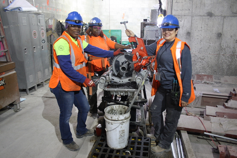 Journeywomen Nuelin Thompson, Tamara Lamond (Forewoman) and Rosalinda Nevarez of Five Star Electric pose in front of a conduit bender on the job at the MTA's East Side Access Project.